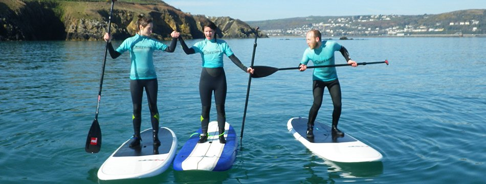 Adults posing for a photo while paddle boarding in West Wales