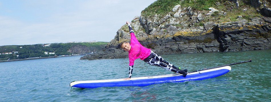 Children stand up paddle boarding in Pembrokeshire West Wales