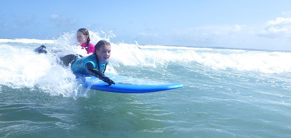 Children enjoying a surf lesson catching waves at Newgale beach in Pembrokeshire, Wales