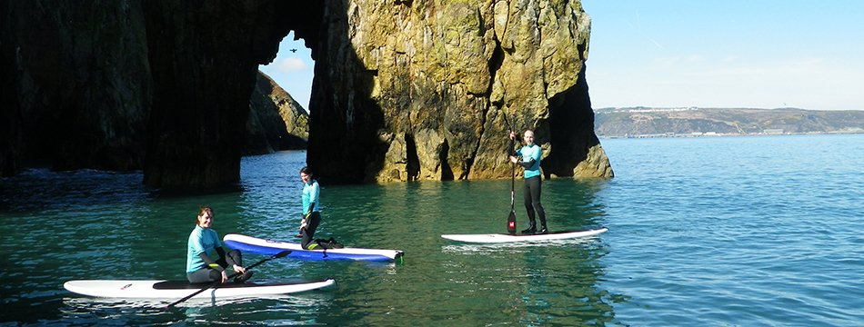 Adults stand up paddleboarding along the North Pembrokeshire Coast from Fishguard Lower Town to Needle rock. We supply all the kit & equipment for your SUP adventure.