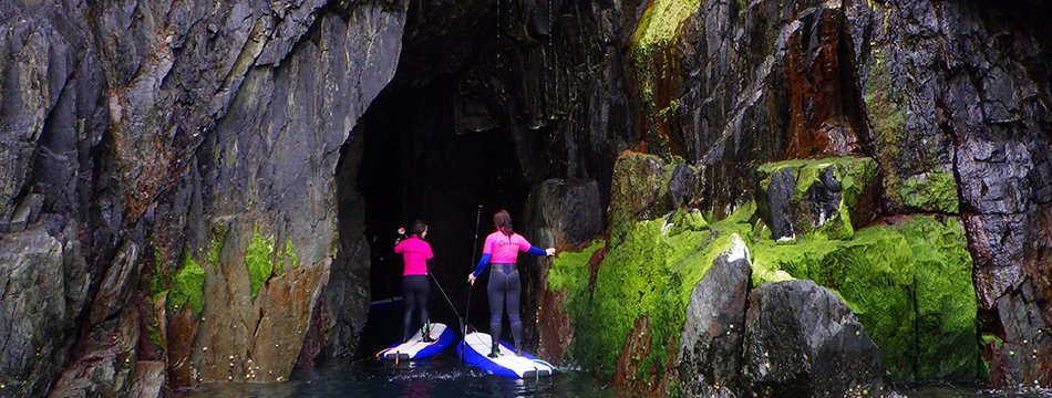 Stand up paddle boarding into sea caves on the north Pembrokeshire Coast with Board Games Surfing. We supply the wetsuits, paddleboards and paddles!
