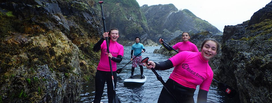 Adults exploring the Pembrokeshire coast while stand up paddle boarding in West Wales with Board Games Surfing