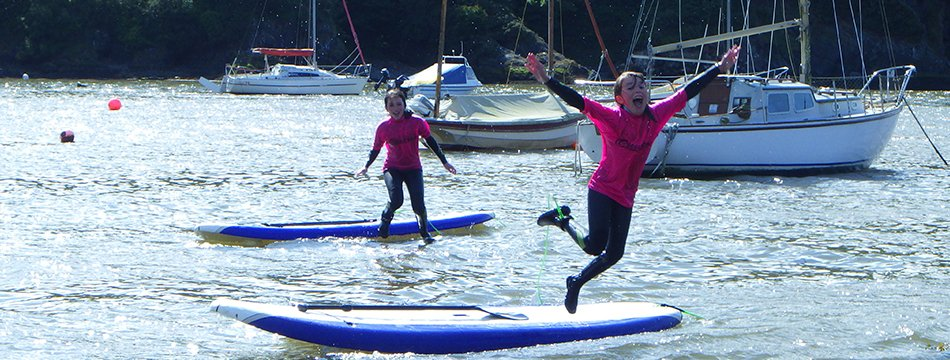 Children jumping in the sea while stand up paddle boarding in Fishguard Harbour, Wales. Learn the basics in the harbour then head out to explore the Pembrokeshire coast by SUP.