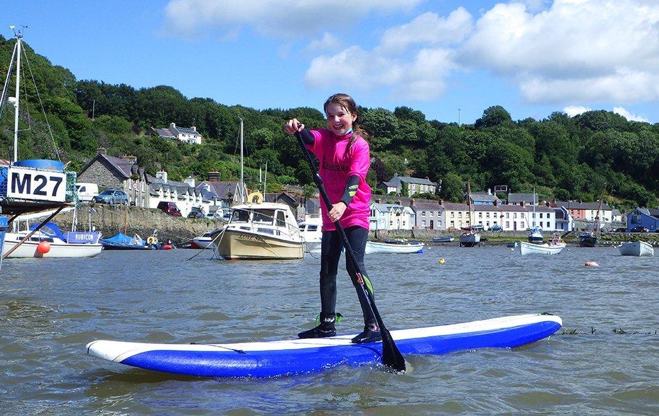 children paddleboarding in Fishguard
