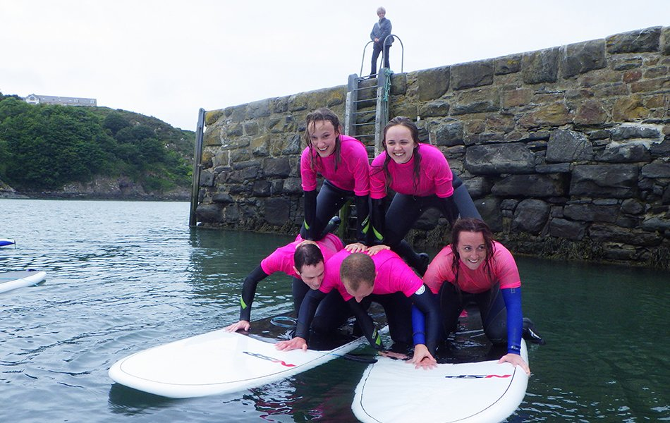 Adults human pyramid on paddleboards