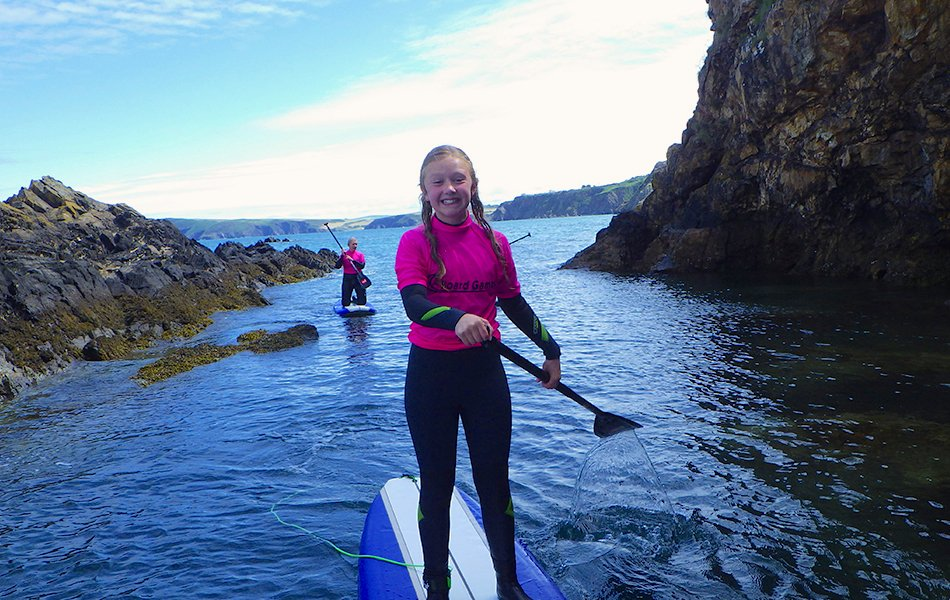 Teenagers paddle boarding in Pembrokeshire