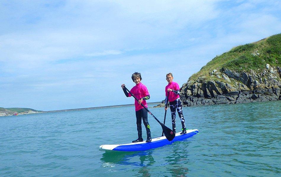 Children paddle boarding in Pembrokeshire