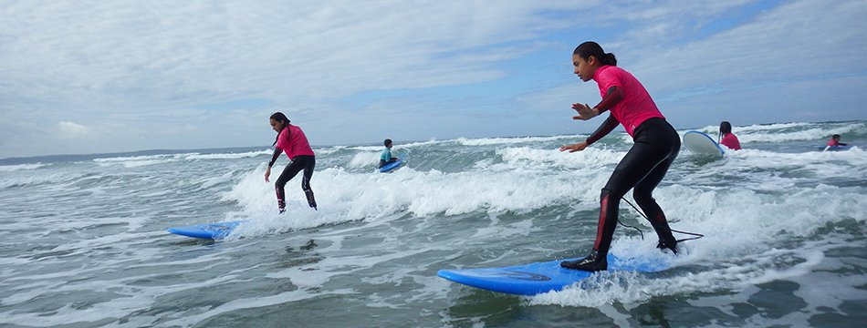 Family enjoying surf lessons at Newgale beach near St Davids, Pembrokeshire. Anyone over 8 years of age can try surfing in Wales.