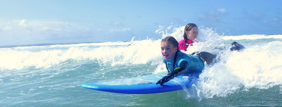 Children surfing waves at Newgale beach while on surf lessons in Pembrokeshire, Wales