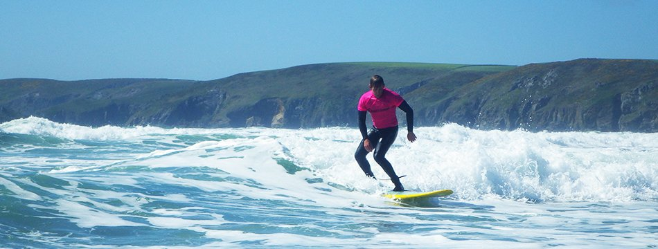 Adults surfing at Newgale beach near St Davids, while on a surf lesson in Pembrokeshire, Wales