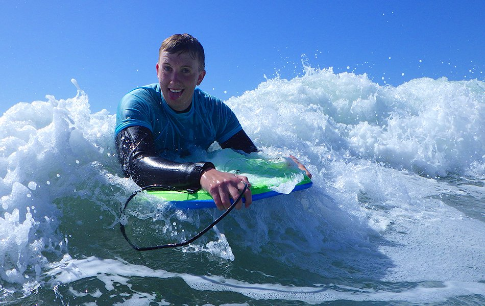 Adults bodyboarding in Wales