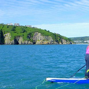 Children exploring the Pembrokeshire coast while paddleboarding in Pembrokeshire, Wales