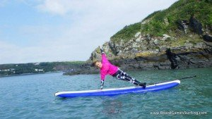 Teenager wearing a cow pattern wetsuit while stand up paddle boarding with Board Games Surfing in Pembrokeshire